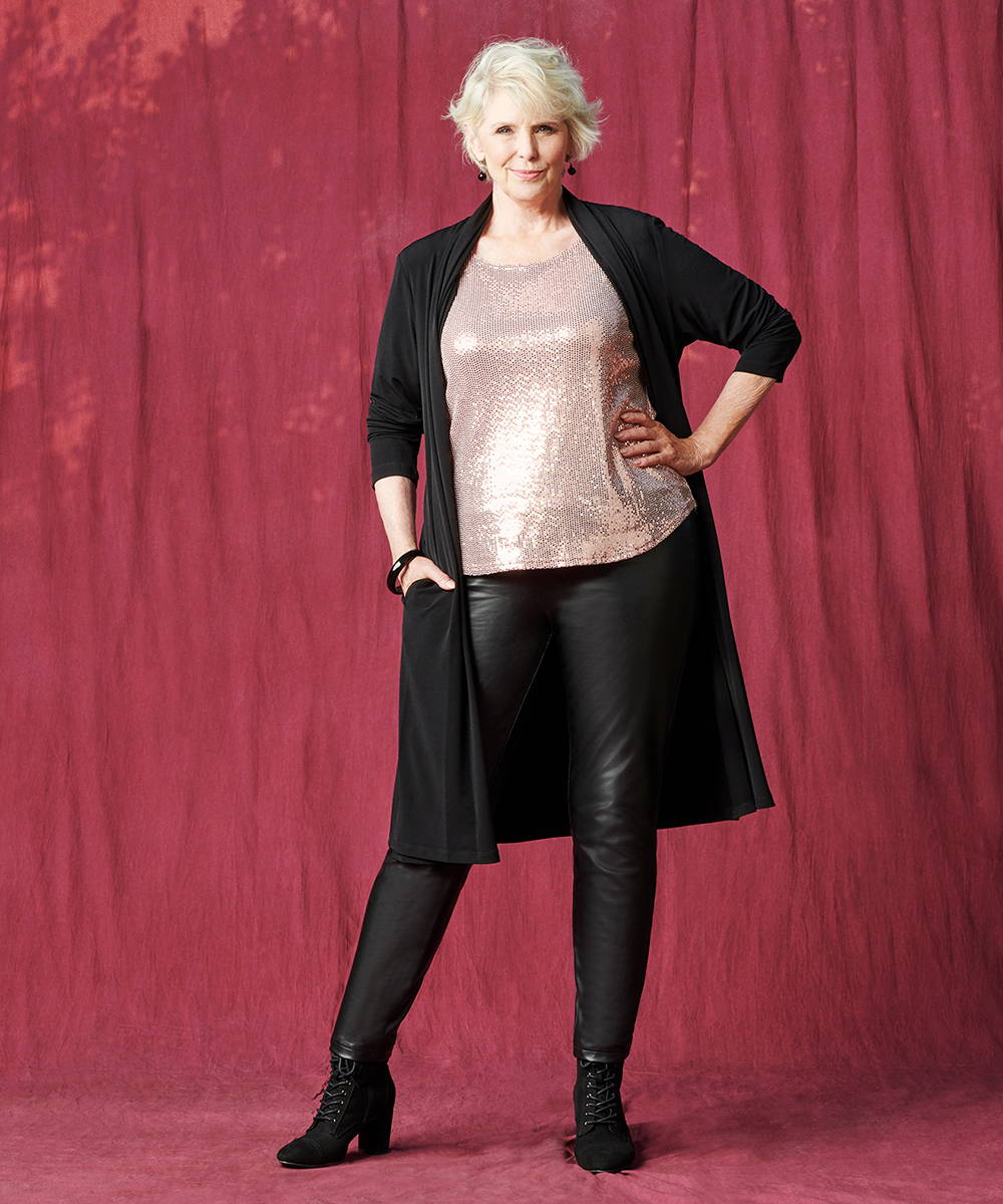 woman wearing rose gold sequin caxlz short sleeve sequin top paired with the caxlz half sleeve bianca black open front cardigan and black pleather pants from lawrence zarian and connected apparel