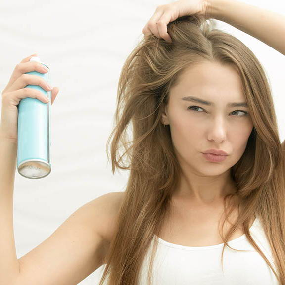 woman spraying dry shampoo