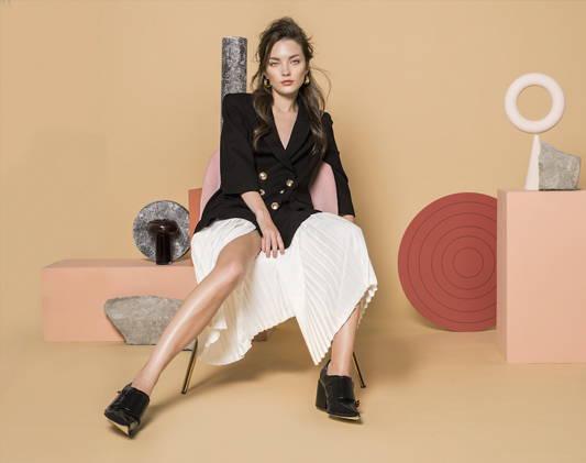 Fashion woman wears a black blazer and white skirt