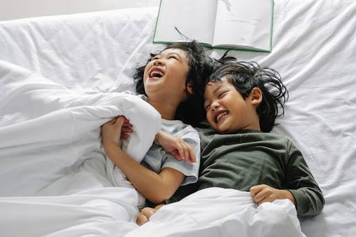 Siblings, a young girl and boy, laughing while laying in bed - Photo by Alex Green from Pexels