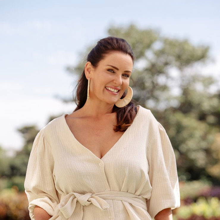 Smiling dark haired beautiful woman wearing large beige earrings and a beige outfit with a v neck