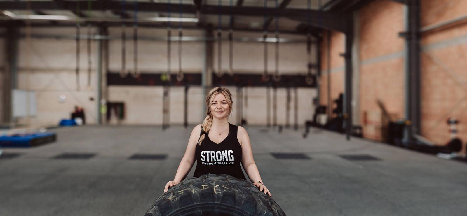 Frau im Fitnessstudio mit einem großen Reifen vorne dran