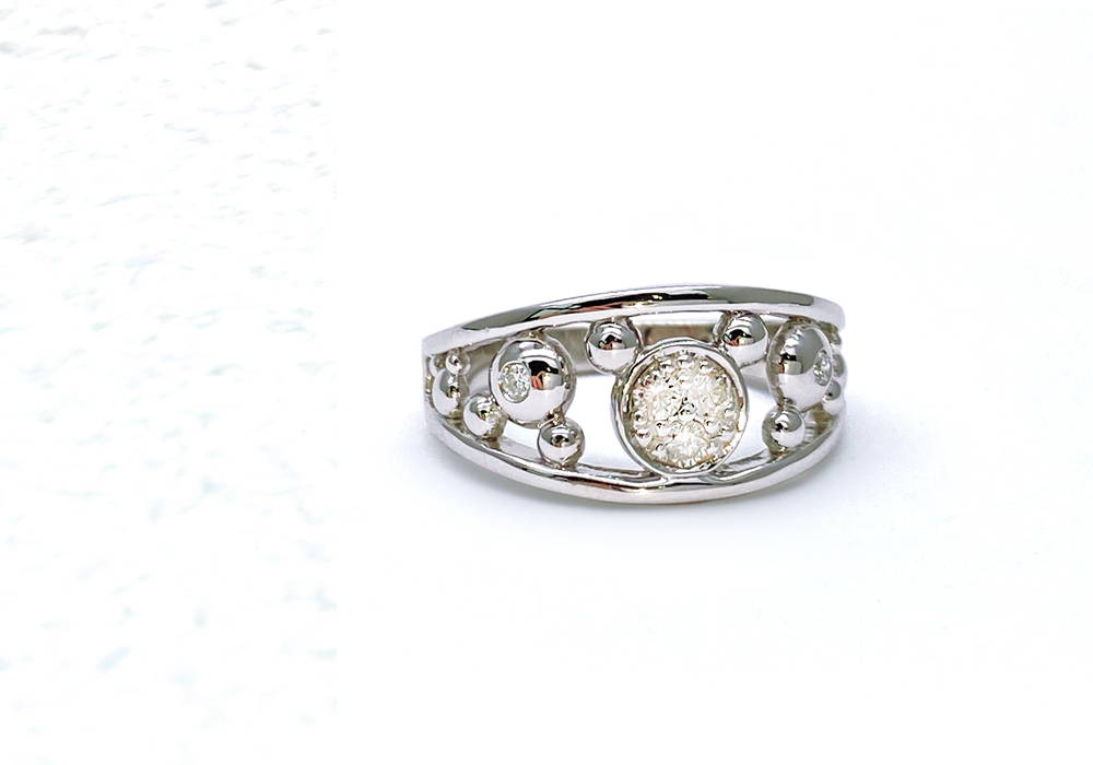 White gold ring with a round diamond in a closed setting in an airy ring body filled with small bubbles