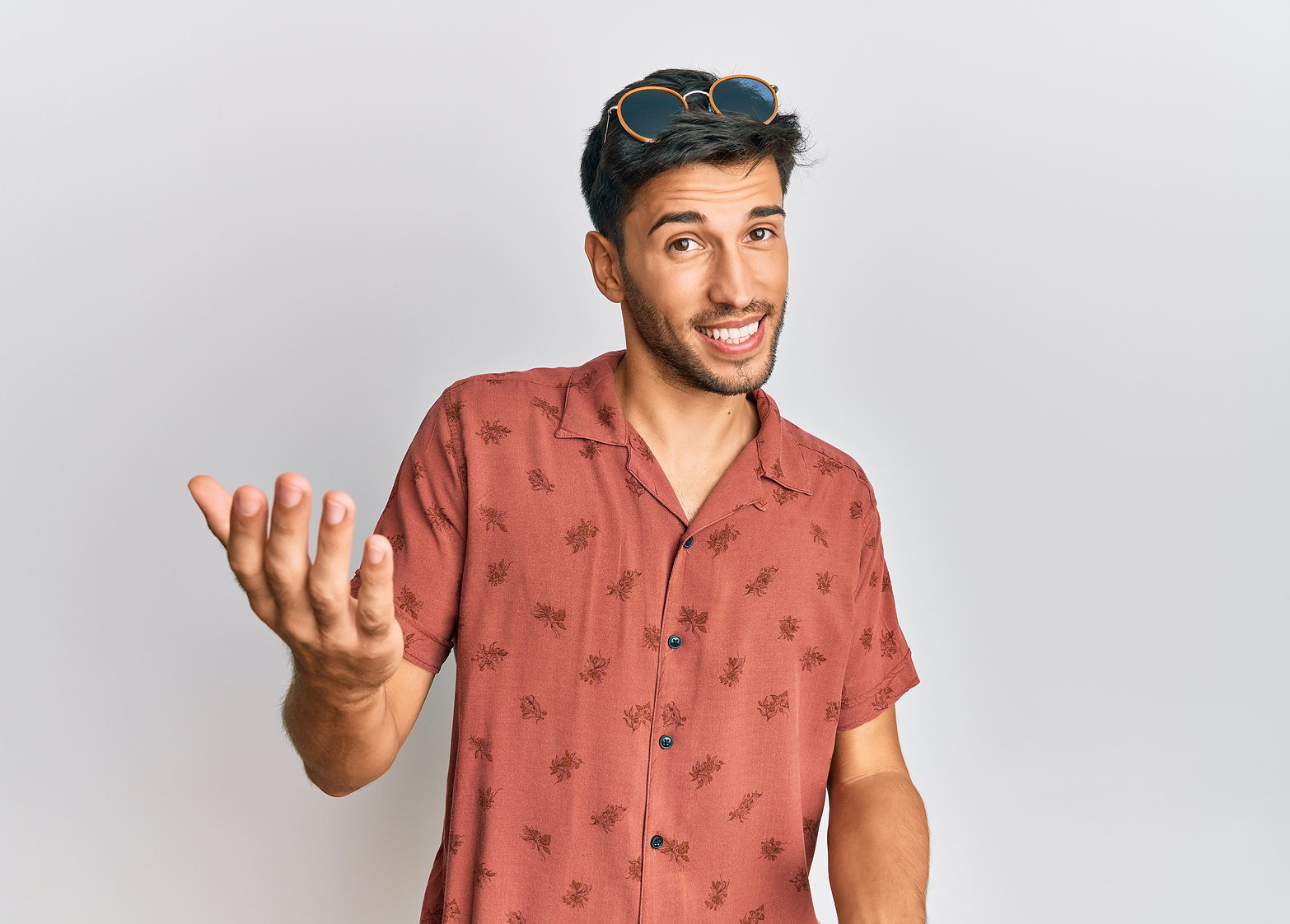 Photo of man wearing a red short sleeve and glasses on his head smiling reaching his hand out to you with white background.