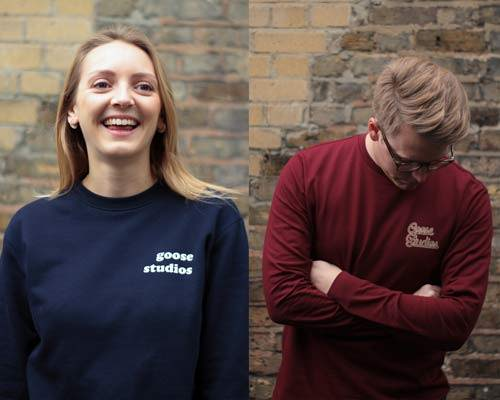 Woman wearing organic cotton navy blue sweatshirt with Goose Studios text logo on left chest and man wearing burgundy organic cotton long sleeve t-shirt with Goose Studios logo, both from sustainable fashion brand Goose Studios