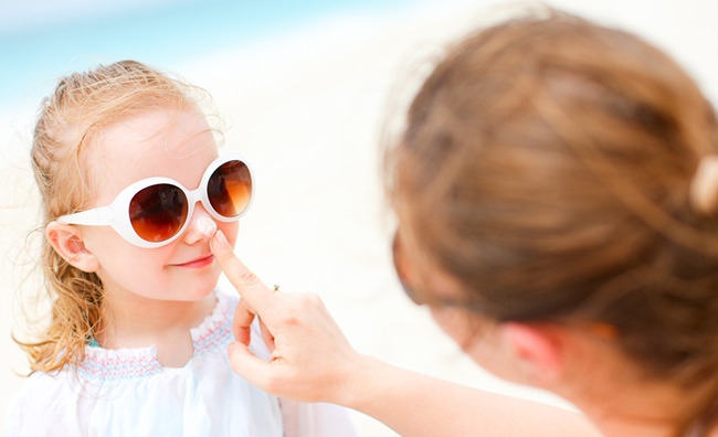 image of mother putting sunscreen on child