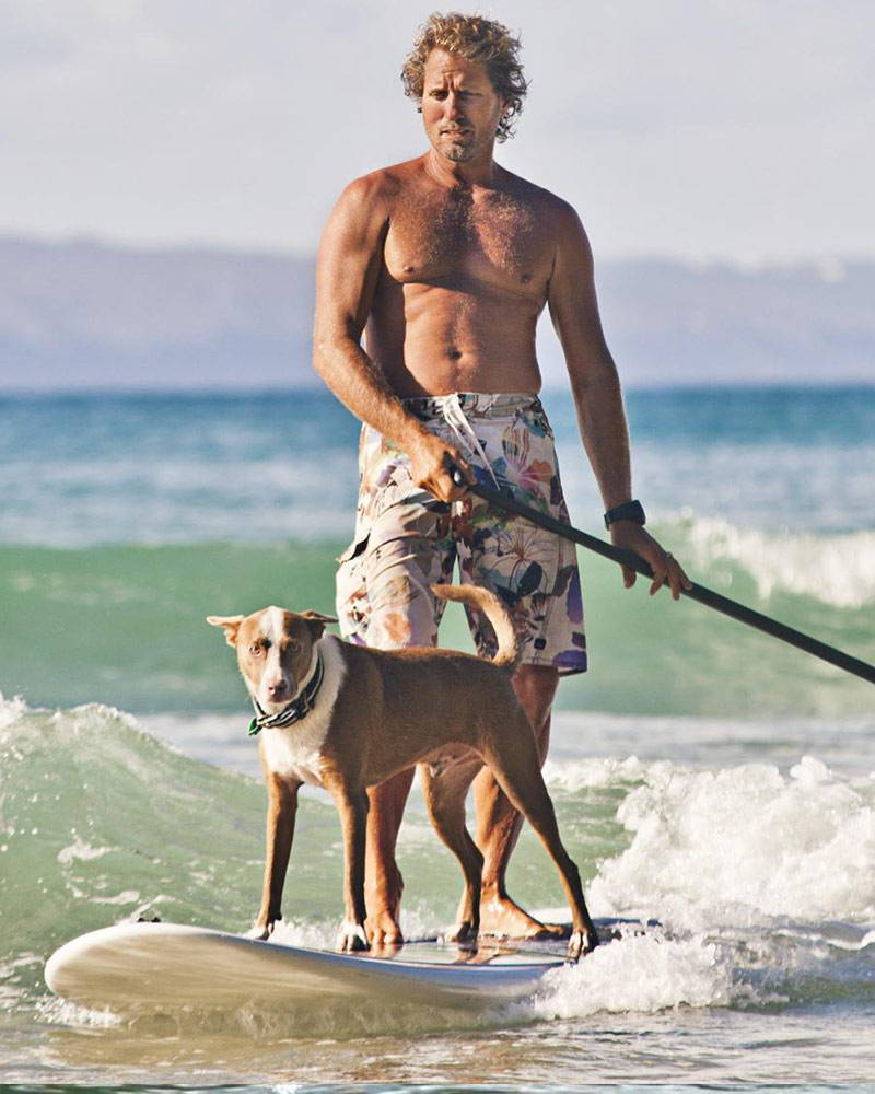 Chris de aboitiz surfing with his dog