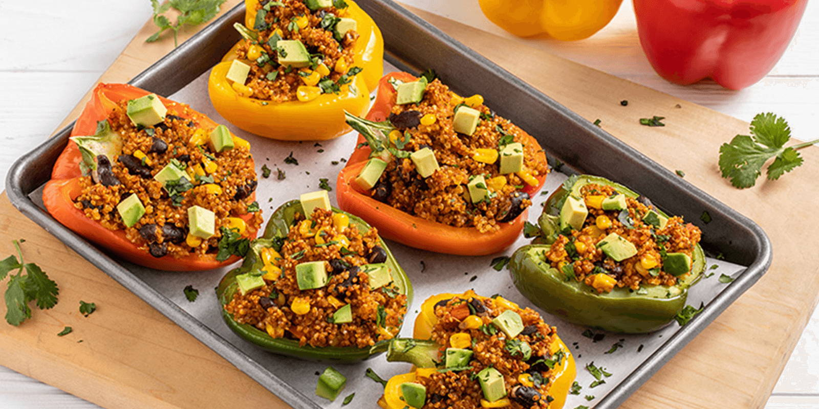 Tray of stuffed bell peppers on a white countertop.