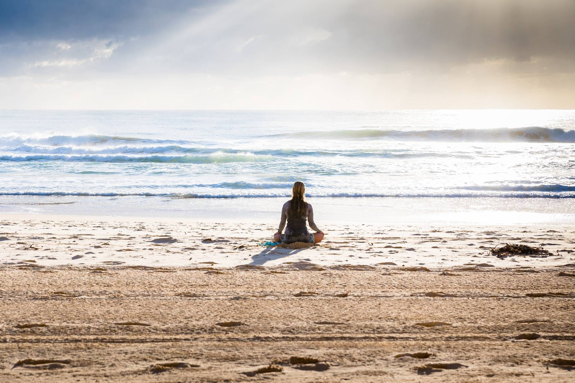 woman sitting in lotus position facing the sea