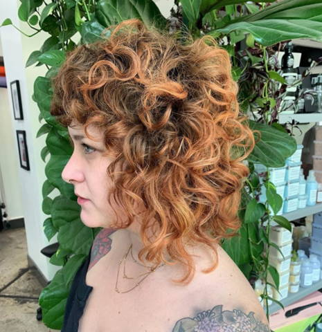 side view of a woman with reddish brown curly hair