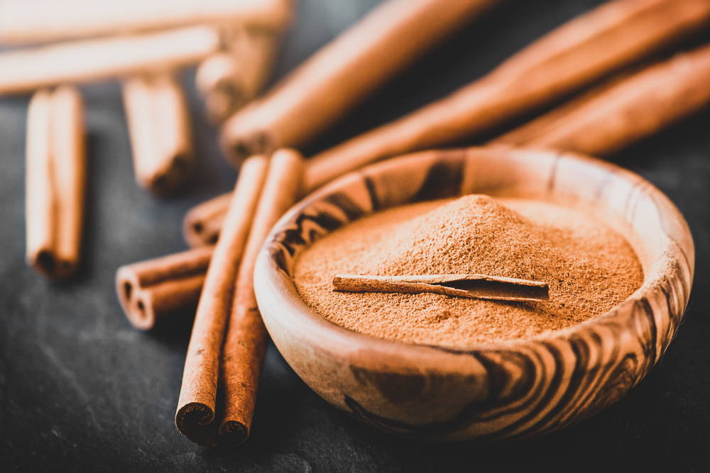 Cinnamon sticks and powder in wooden bowl