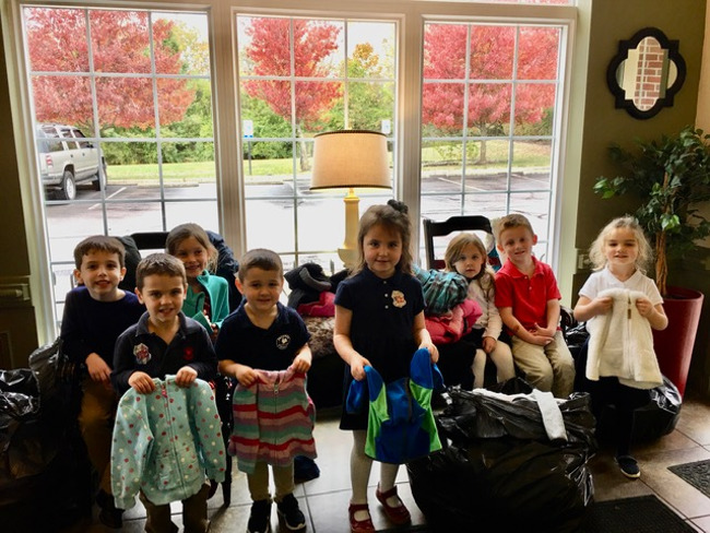 Children with coats they are donating