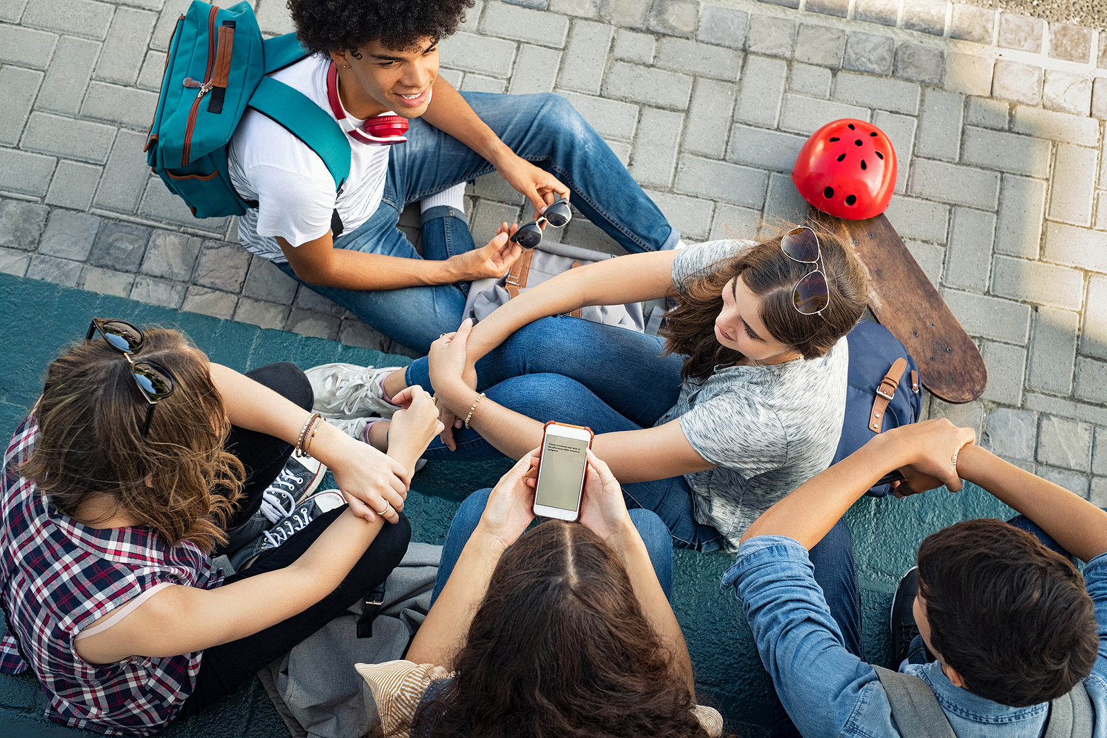 Image of a high angle view of guys and girls sitting and talking together. They are a Cheerful group of happy friends in conversation after class
