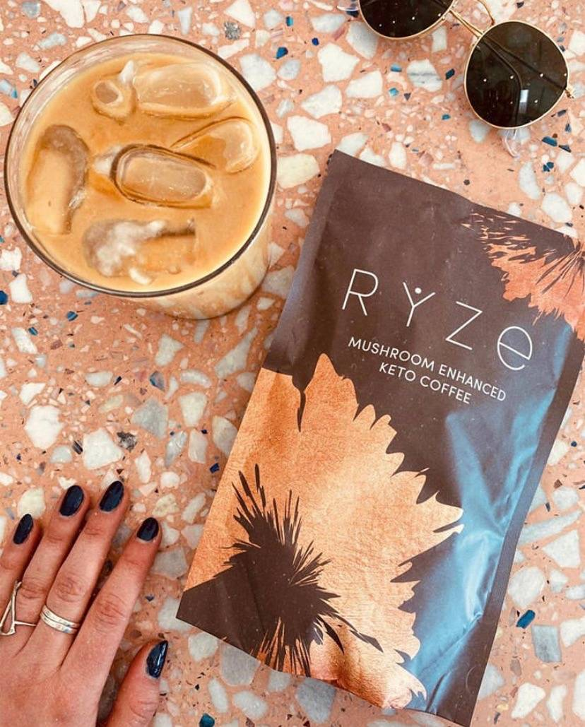 Bag of RYZE mushroom coffee with glass of iced coffee and sunglass on the table