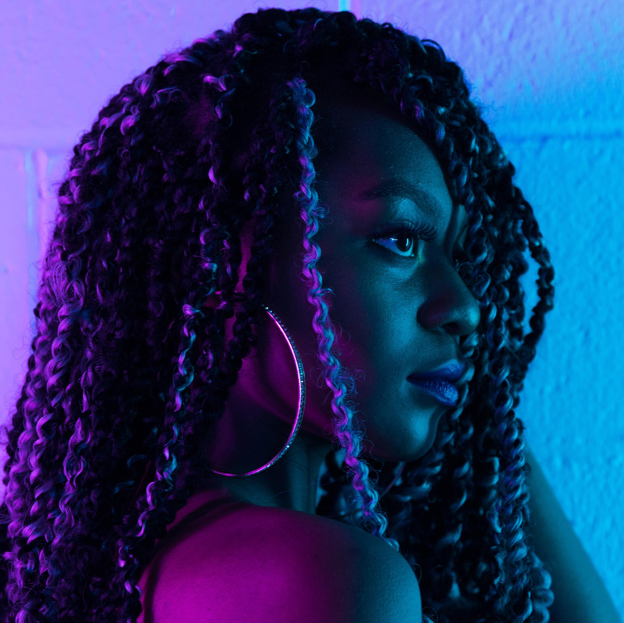 A black woman with long curls surrounded by the bi colors, she is looking forward.