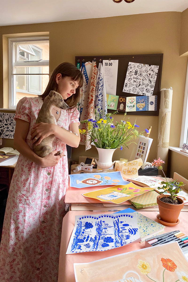 Polly Fern in her studio wearing the cotton Country Vine Valentina Dress holding her puppy