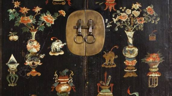Detail from one of a pair of antique black lacquer wedding cabinets with painting of lucky symbols and original brass from the Qing dynasty.