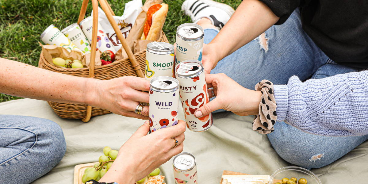 Picnic basket surrounded by light snacks with Kiss of Wine Sauvignon Blanc, Riesling and Rose cans.