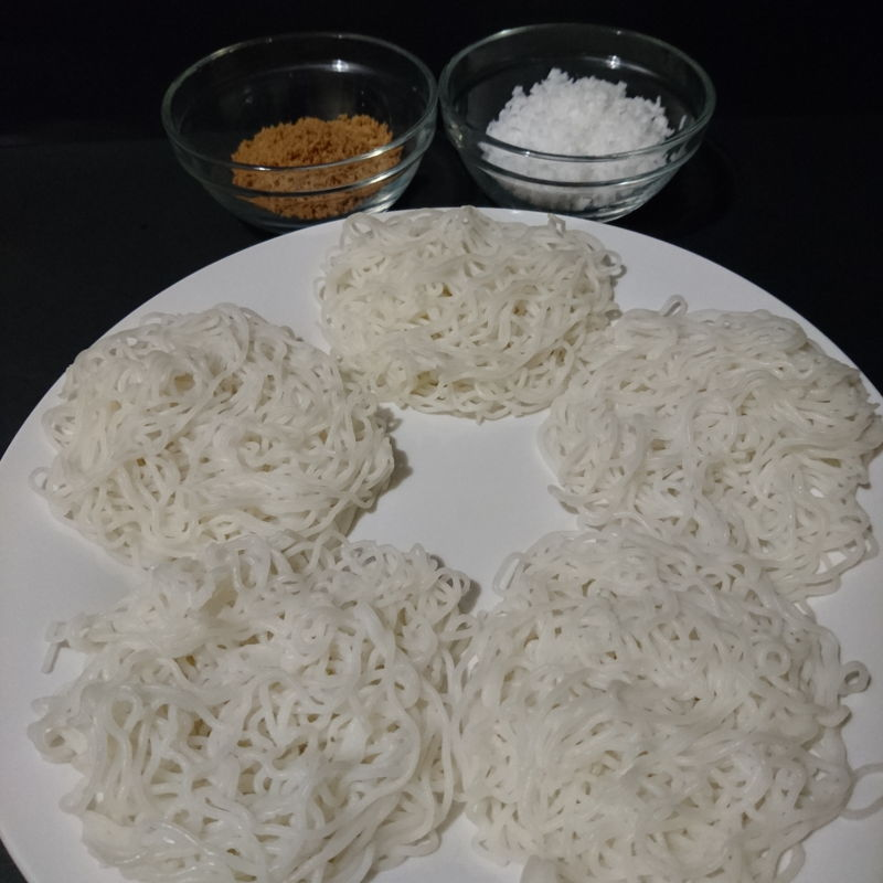 Idiyappam served with grated coconut and brown sugar.