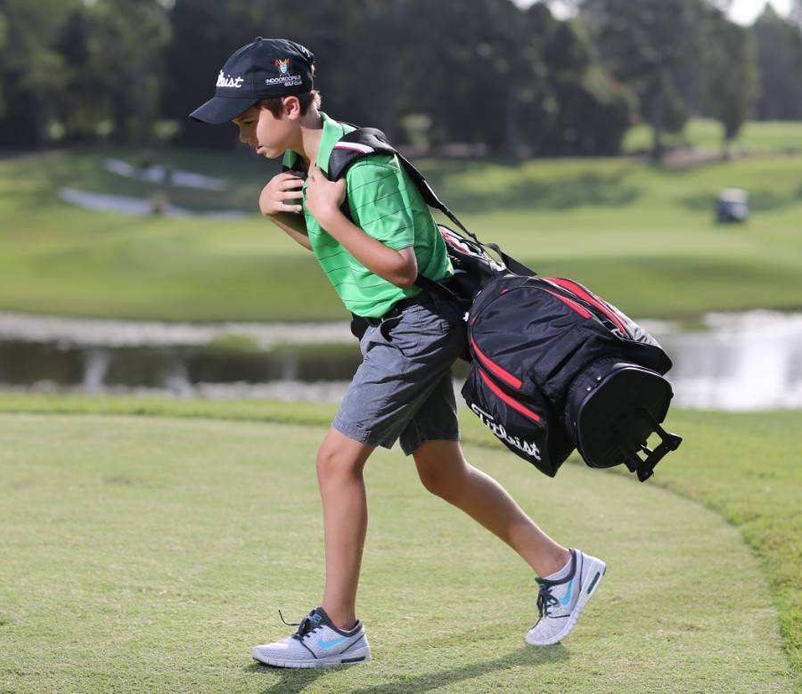 Boy carrying his golf bag