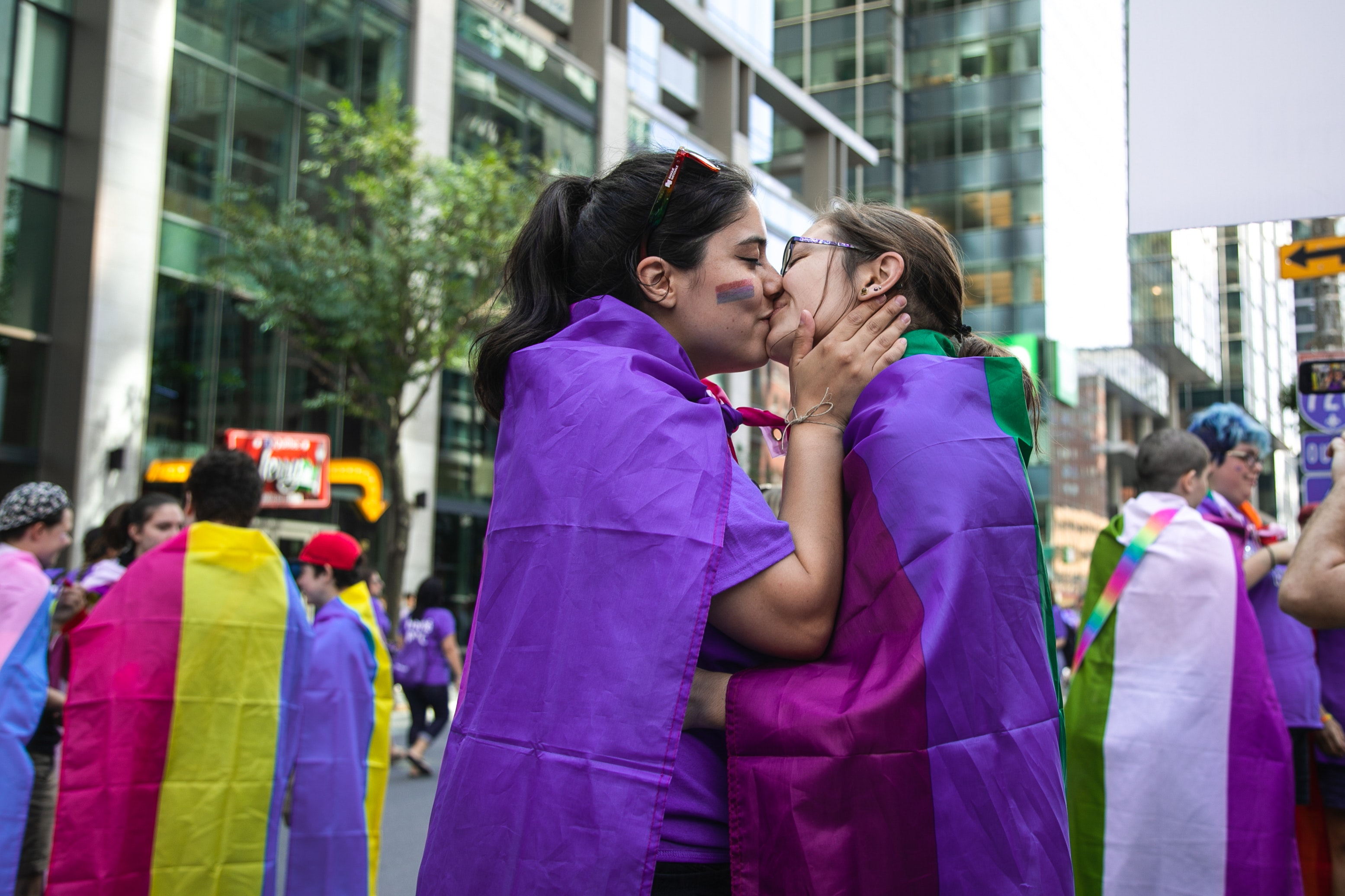 Image of two young women with long hair in the middle of the street during a pride parade, both wearing the bi flags as blankets kissing while one has her hands on the other girls' face.