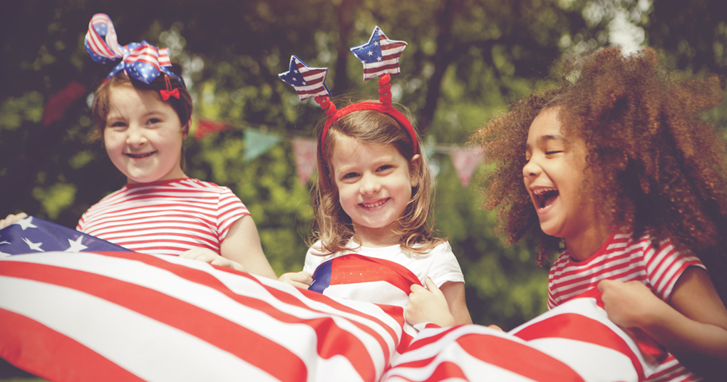 Three young girl wearing red, white and blue head bands wave a large American flag to celebrate fourth of July