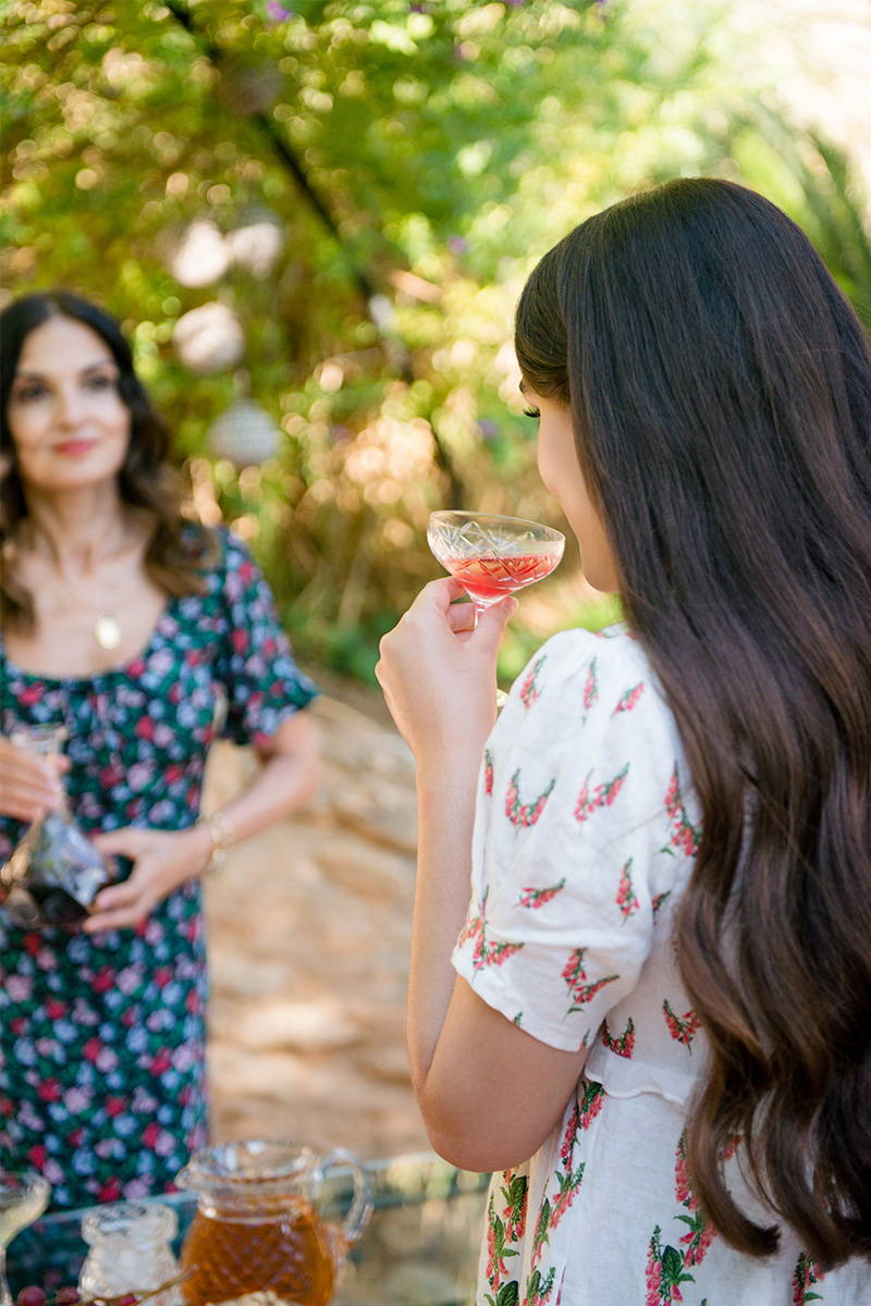 Madeline Mills sips on champagne whilst wearing YOLKE