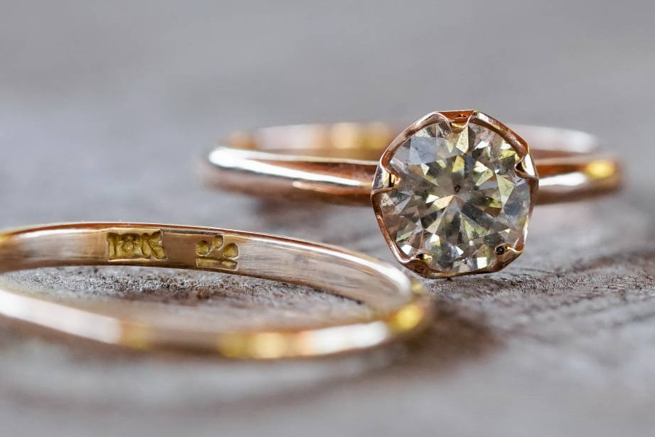 A custom ethical gold diamond ring with 18 karat stamp.