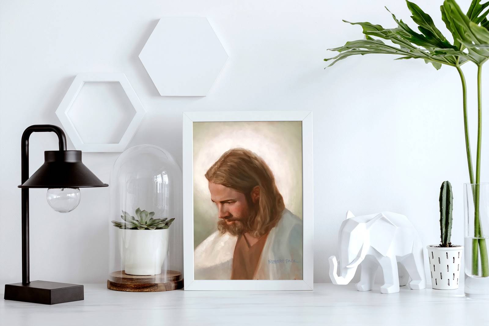 A small art portrait of Christ arranged next to a desk lamp and various other small items.