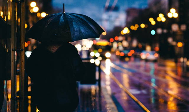 Men with umbrellas stand on the street in the misty rain of night