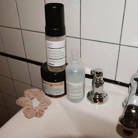 Davines hair products on the ledge of a bathroom sink