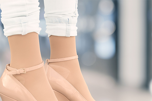 A pair of woman's legs in high heels wearing beige opaque compression stockings