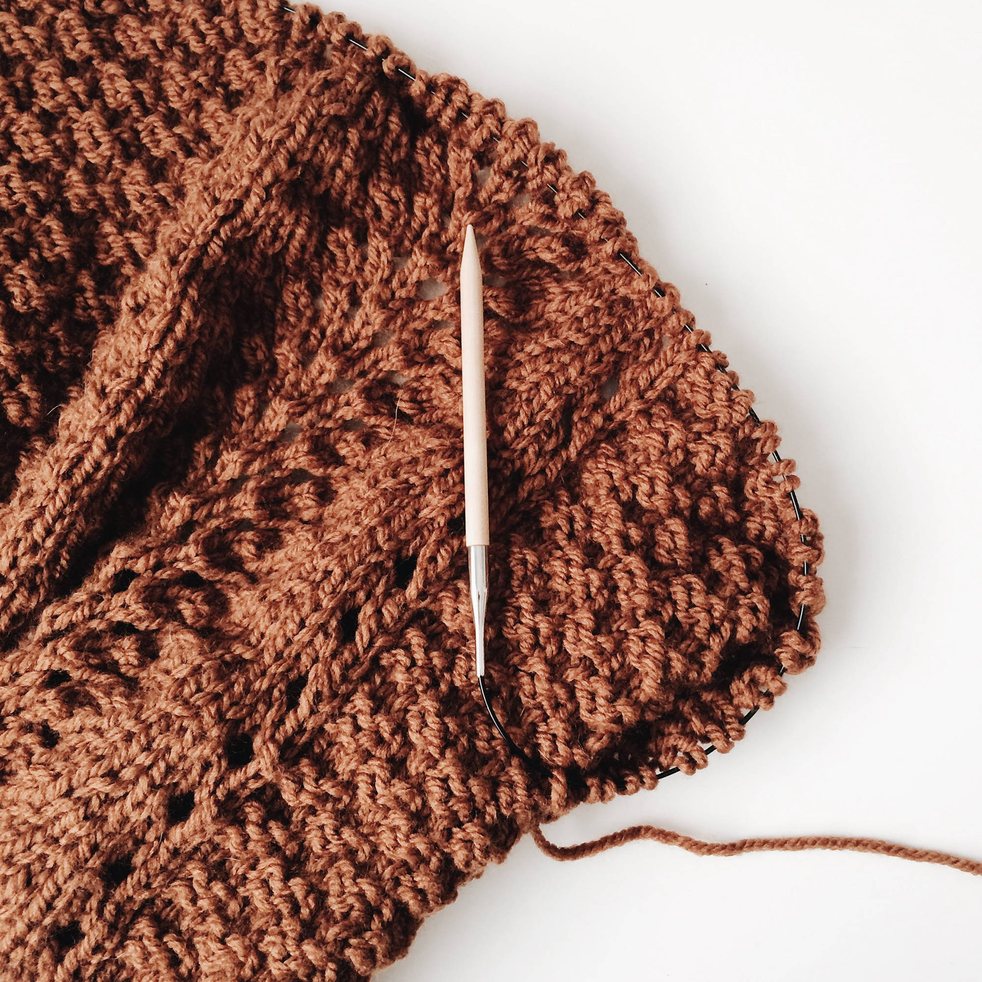 detail of a wool sweater with a wood knitting needle