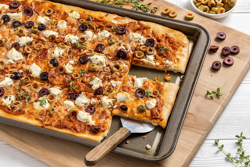 Spatula serving flatbread topped with olives.