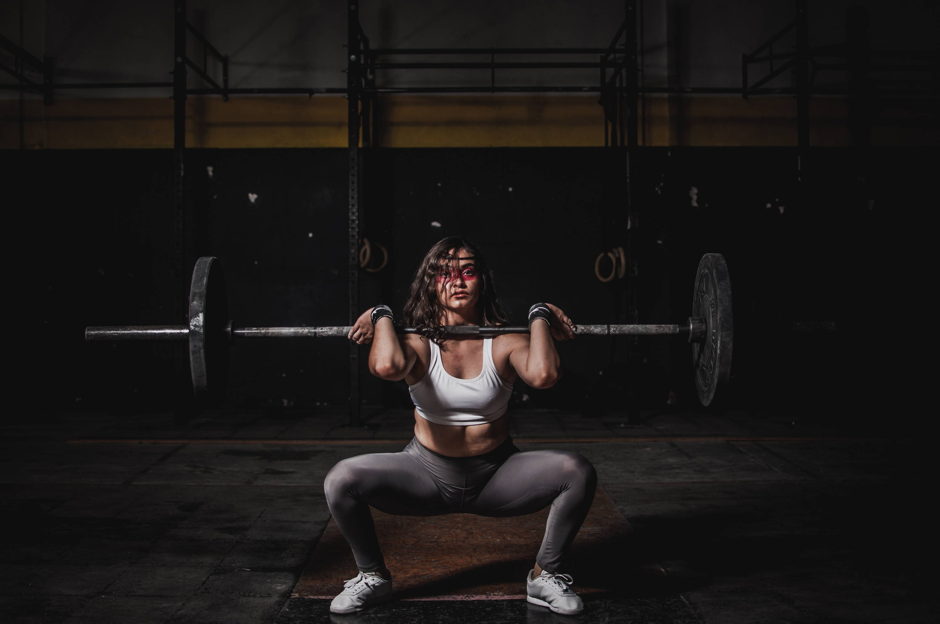 Strong woman squatting with a weight