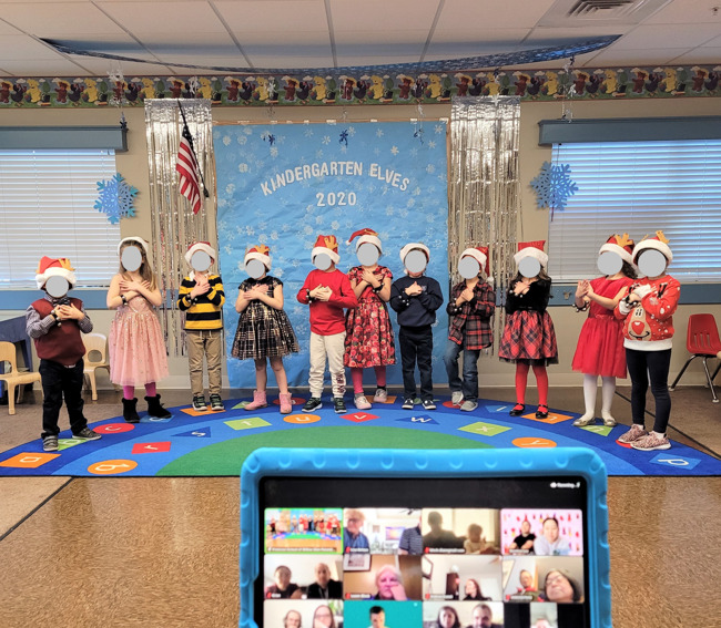 Kindergarten class performing their songs with the iPad showing parents on Zoom