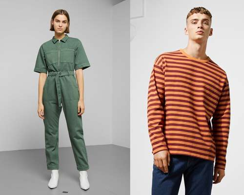 Woman wearing organic cotton khaki green jumpsuit with white ankle boots and man wearing orange and burgundy striped oversized long sleeve t-shirt with blue indigo jeans from sustainable fashion brand Weekday