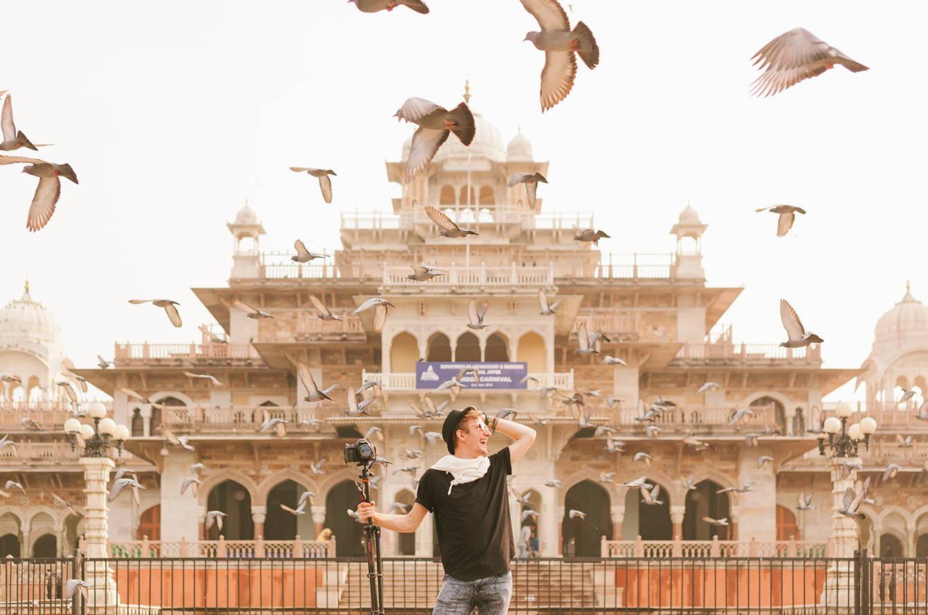 Fotógrafo con su cámara sobre un trípode bajo una bandada de palomas