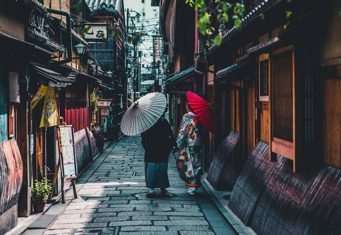 "Geishas with traditional oil-paper umbrellas ""Wagasa"" walking down the streets of Kyoto, Japan"