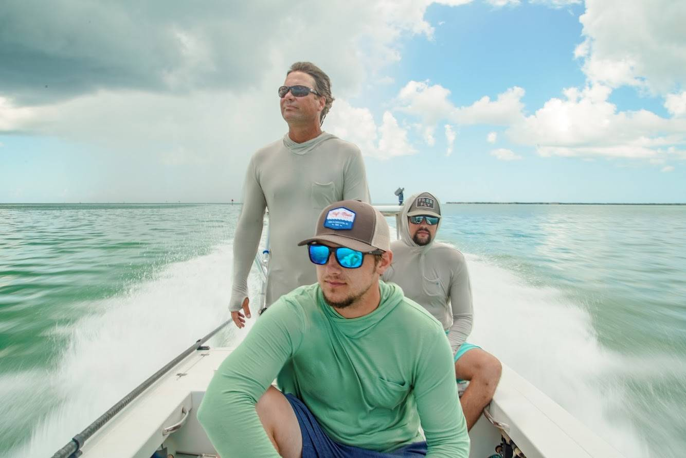 Three fishermen wearing Rheos protective sunglasses speed through the open seas.