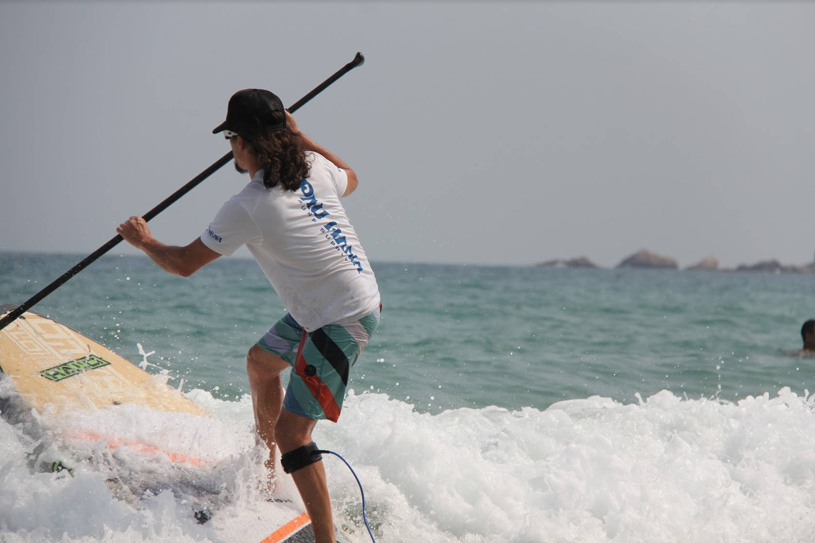 Todd surfing on his surf sup in china catching tropical waves