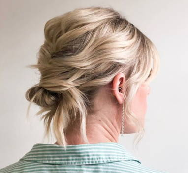 photo of backview of a blonde woman's hair in a low bun hairstyle