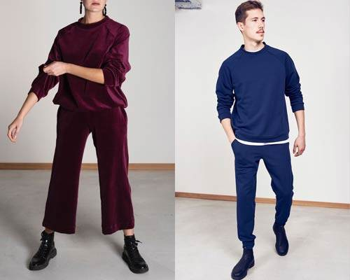 Woman wears organic cotton burgundy velvet sweatshirt and matching wide leg cropped trousers and man wears blue jersey sweatshirt with matching sweatpants from sustainable fashion brand Jann 'n June
