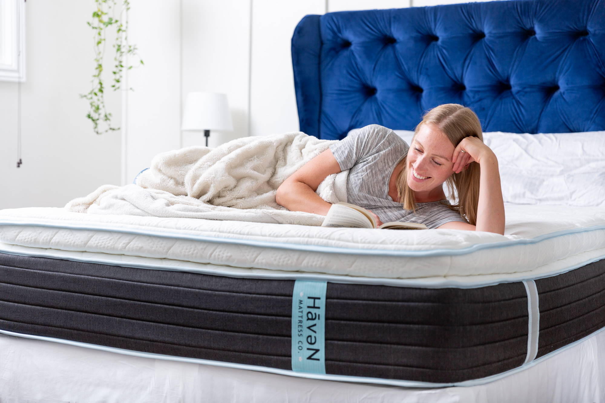 """Interior designer Suzanne Kryton lays comfortably while reading on her 14"""" Lux Hybrid Haven Sleep Co mattress. Blue velvet tufted headboard, white walls, hanging plant, white lamp."""