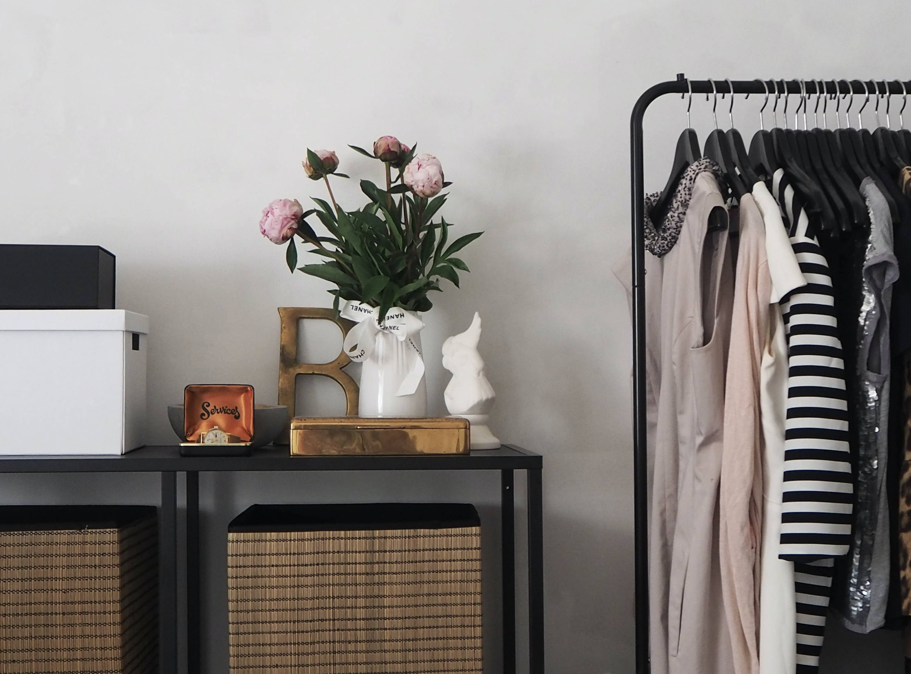 Stylish clothes rack and cupboard with flowers and other decorations