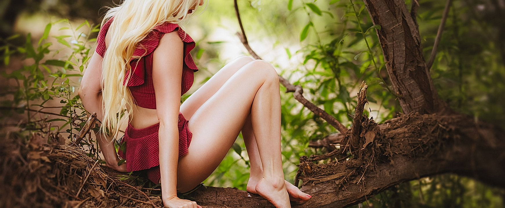 long blonde hair girl sitting on a tree in red ruffled bikini