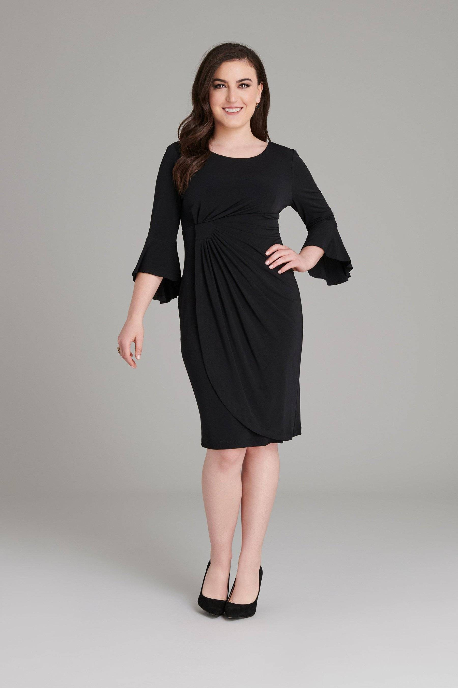 petite dark haired woman in black three-quarter sleeve faux wrap knee-length connected apparel dress with flounce sleeve