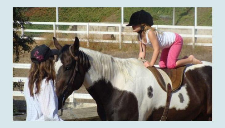 iris brosen kind kniet auf pferderücken