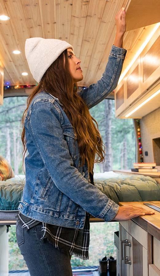 Woman Opening Storage in Custom Sprinter Van Conversion - The Vansmith in Colorado