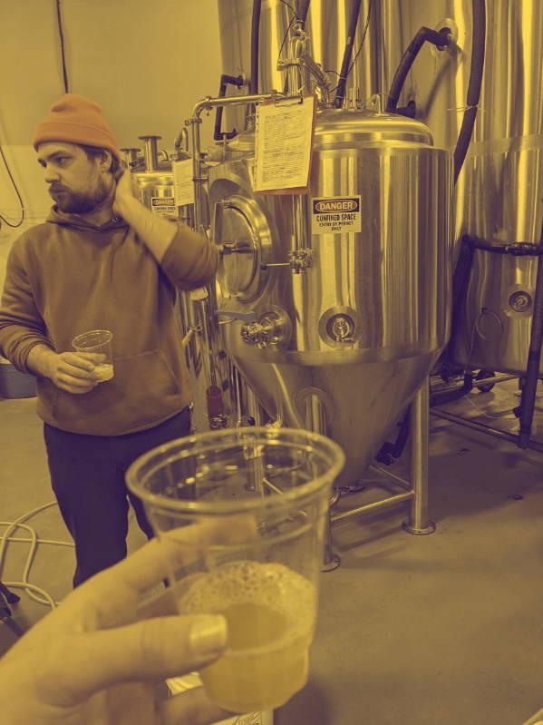 Man standing beside a beer vat.